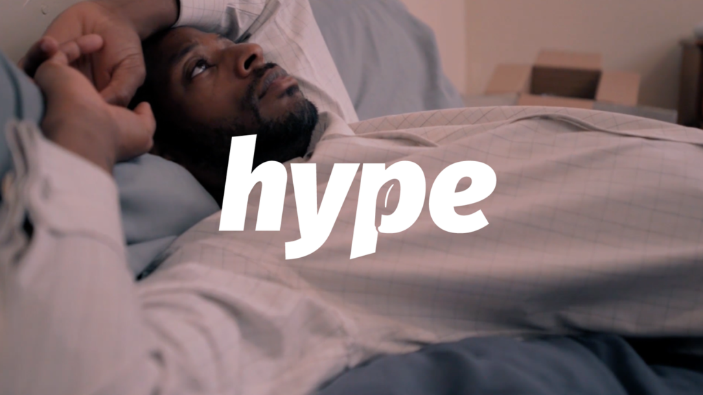"Main Character of hype in a white shirt, laying n blue sheets. The word ""Hype"" is written is white lettering"