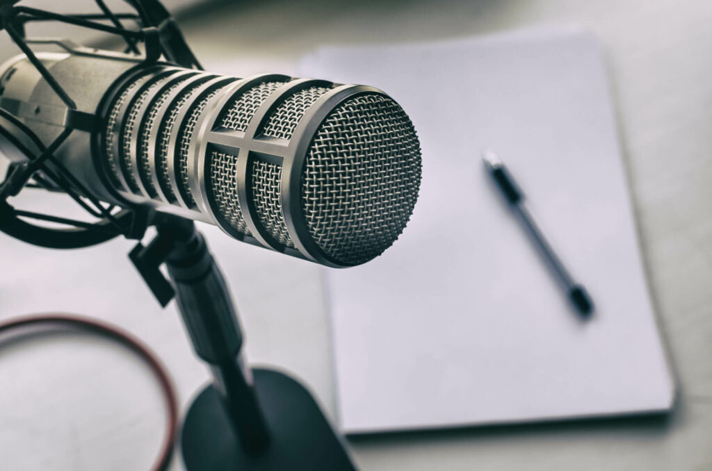 Silver mic with a white pad of paper and a black pen.