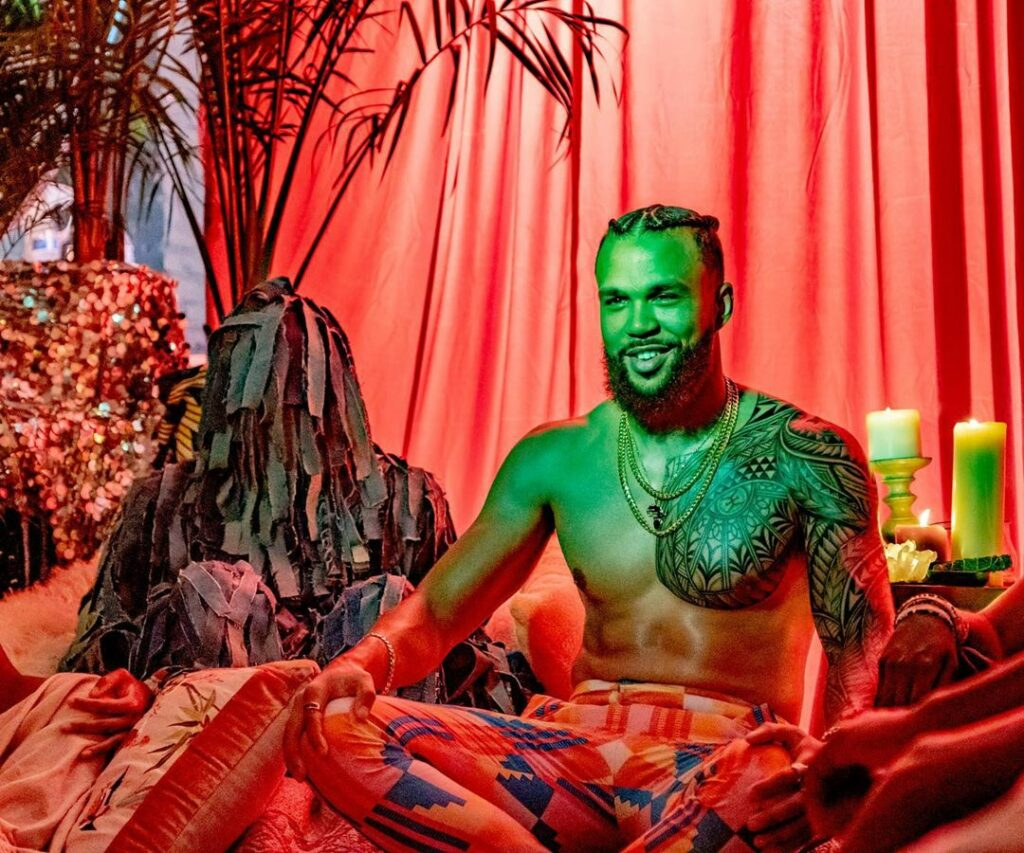 Jidenna is sitting in front of a red curtain. He is sitting in front of a table with white candles. Jidena is wearing gold chains and colorful pants with shapes.