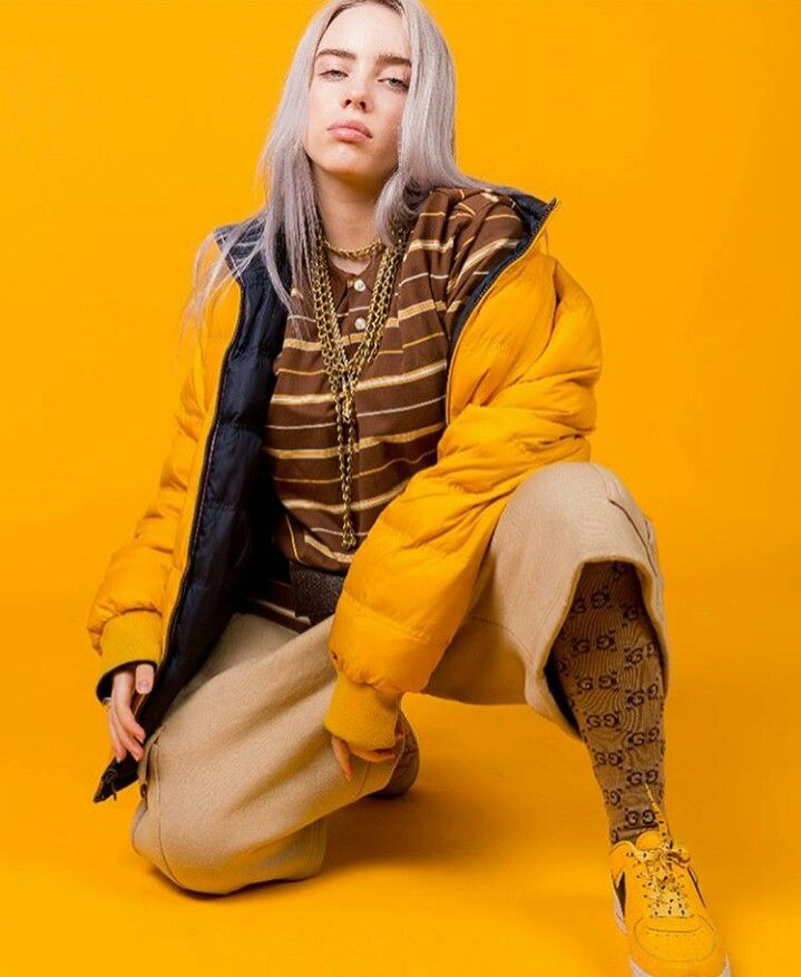 Billie Ellish is wearing a yellow jacket. She has on a brown and yellow striped shirt. She has on tan pants and brown socks with yellow shoes. The background is yellow
